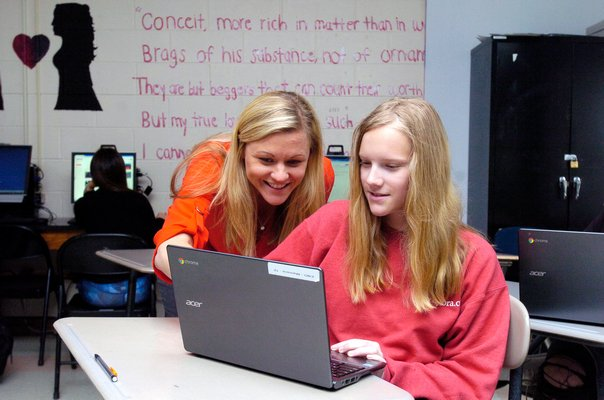Katelyn Maresca, left, gives her student Morgan Phillips suggestions on her article for The Tide.