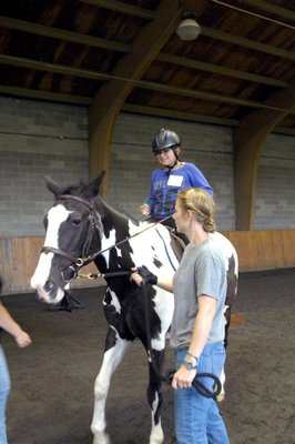 Southampton Intermediate School Principal Timothy Frazier gets a riding lesson from the girls at their graduation from the program on Monday at Wollfer Stables in Sagaponack. DANA SHAW