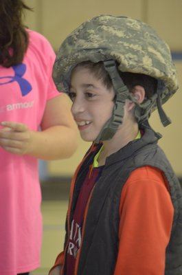 Remsenburg-Speonk Elementary School fourth-grader Manuel Lopez demonstrates a helmet used by members of the ANG's 106th Rescue Wing and prepared care packages on Thursday. BY ERIN MCKINLEY