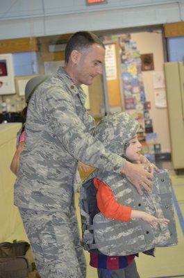 Major Stewart Morrison puts a vest on a Remsenburg-Speonk Elementary School student. BY ERIN MCKINLEY