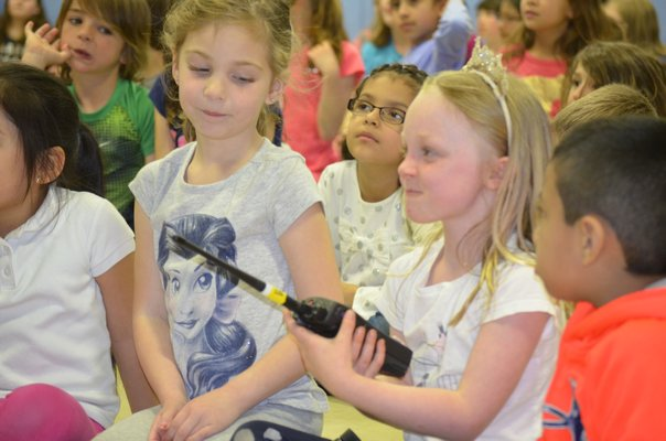 Remsenburg-Speonk Elementary School student Delilah Tunney uses a walkie-talkie at a demonstration about life as part of the ANG's 106th Rescue Wing. BY ERIN MCKINLEY