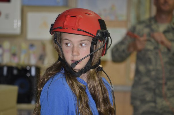 Student Ella Carriero demonstrates a helmet during a presentation with the ANG at Remsenburg-Speonk Elementary on Thursday. BY ERIN MCKINLEY