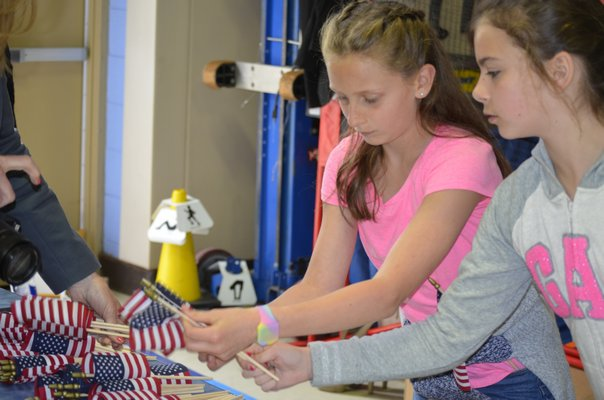 Joley Schaumloffel, left, and Cassandra Dennehy,  fifth-graders at Remsenburg-Speonk Elementary School, help stuff care packages for soldiers over seas. BY ERIN MCKINLEY