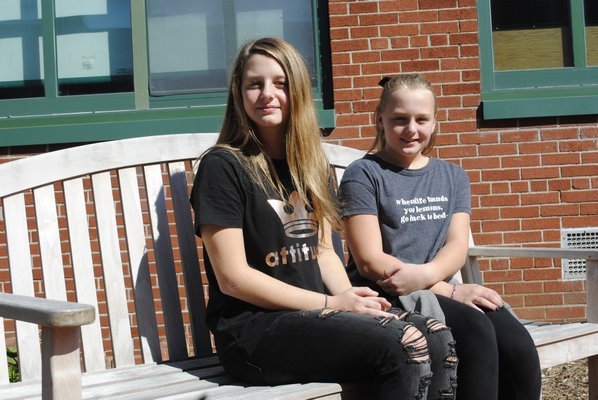 Emily Kyea, left, and her sister Brooke Kyea in the reading garden that was dedicated to their father. AMANDA BERNOCCO