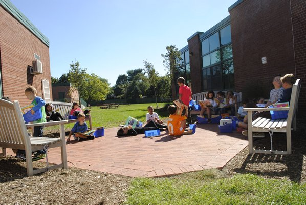 Students enjoy some books in the East Quogue reading garden. AMANDA BERNOCCO