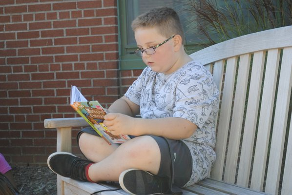 Bruce Phillips III reads a book in the East Quogue reading garden. AMANDA BERNOCCO