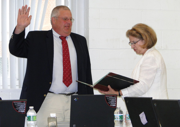 Southampton School District Clerk Mary Pontieri reads the oath of office to School Board Vice President Don King on July 7.