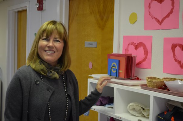 Director of the Southampton Montessori School Irene Hope Gazza showing off student artwork. BY ERIN MCKINLEY