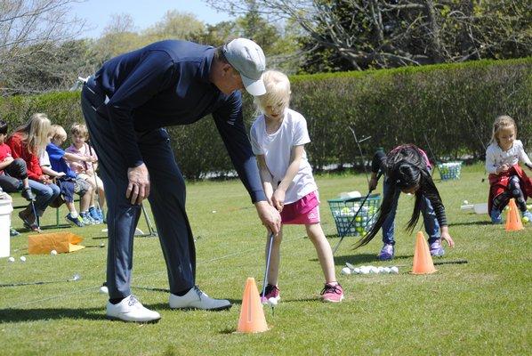 Sophia Zaleski, a kindergartener, practices golfing with Rich Stuckiln. AMANDA BERNOCCO