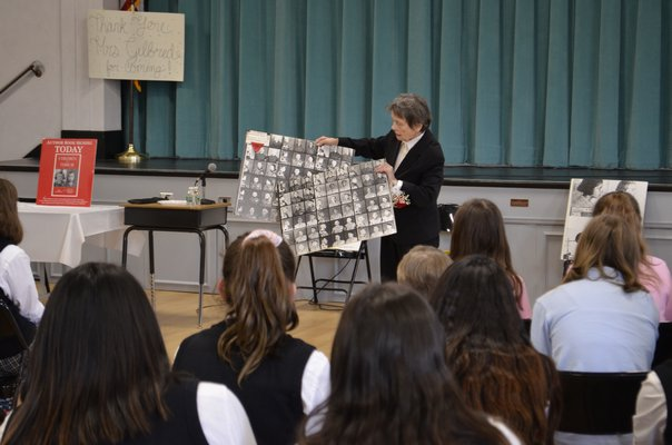 """Bozenna Urbanowicz Gilbride showing photos of teenage prisoners from the Holocaust. """"Are you scared of what hatred does if we don't change?"""" she asked the students. ANISAH ABDULLAH"""