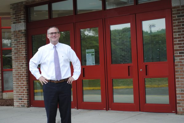 Superintendent Lars Clemensen stands in front of the enterance of the Hampton Bays High School, which will be under construction starting on June 26. AMANDA BERNOCCO