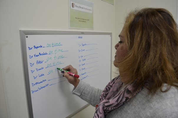 Westhampton Primary Care Center Site Administrator Maria Barlowe informing patients which doctors are in that day on a white board displayed in the waiting room. ANISAH ABDULLAH