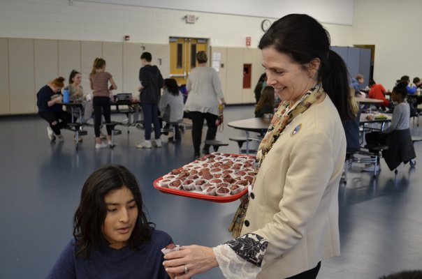 Regan Kiembock handing out beet muffins to students at Southampton Intermediate School. ANISAH ABDULLAH