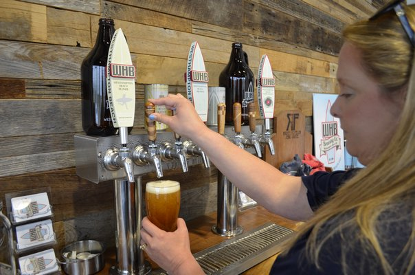 Co-owner Kate Tedesco pouring a beer at Westhampton Beach Brewing Company. ANISAH ABDULLAH