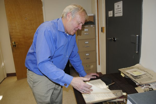 Southampton Town Historian Zach Studenroth flips through a book of handwritten Hampton Bays minutes from the early 1900s. AMANDA BERNOCCO