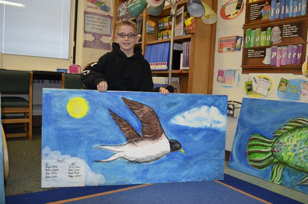 Kevin Smith, 11, shows a celing tile he helped paint at Westhampton Beach Elementary School. BY ERIN MCKINLEY