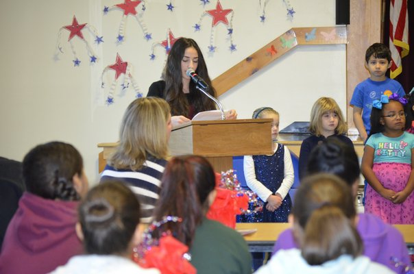 Kaitlin Kirshy reads her patriotic speech at a Veteran's Day breakfast at the Tuckahoe School on Monday. BY ERIN MCKINLEY