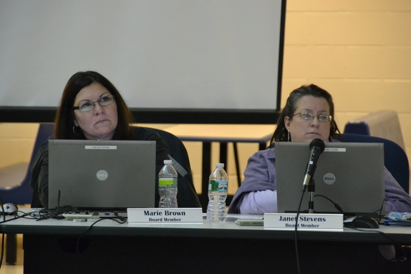 School board members Marie Brown and Janet Stevens look on as community members address the board at Wednesday night's meeting. LAURA COOPER