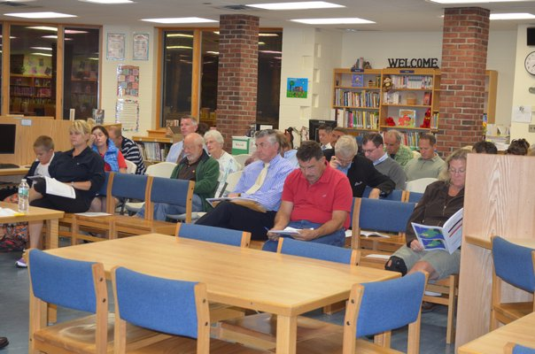 The community listens to a presentation at the merger study meeting held at the Tuckahoe School on Thursday. BY ERIN MCKINLEY