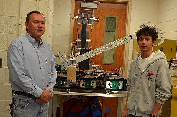 Westhampton Beach Robotics Team moderator Tony Kryl and senior Nick Panzarino with previous robots built by the team. ERIN MCKINLEY
