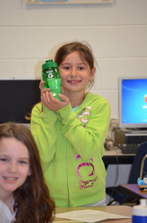 Edona Popi holds up her reusable water bottle during class.