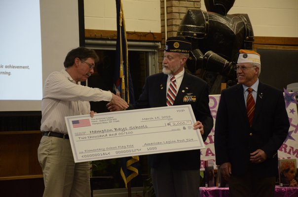 Members of the American Legion Hand-Aldrich Post 924 present a $2,000 check to the Hampton Bays Board of Education at Tuesday night's meeting, to replace a flag pole in front of the elementary school that was blown down in a snow storm in February. Pictured left to right, Hampton Bays Board of Education President Rich Joslin, Richard Steiber and William Hughes. GREG WEHNER