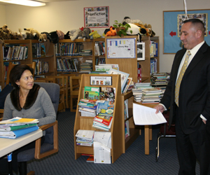 Charles Russo, the superintendent of East Moriches School District, reads a letter; Remsenburg/Speonk Superintendent Katherine Salomone listens on at the school district's board of education meeting. JESSICA DINAPOLI