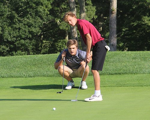 East Hampton's Turner Foster, and his teammate Nate Wright, watch his putt. KYRIL BROMLEY