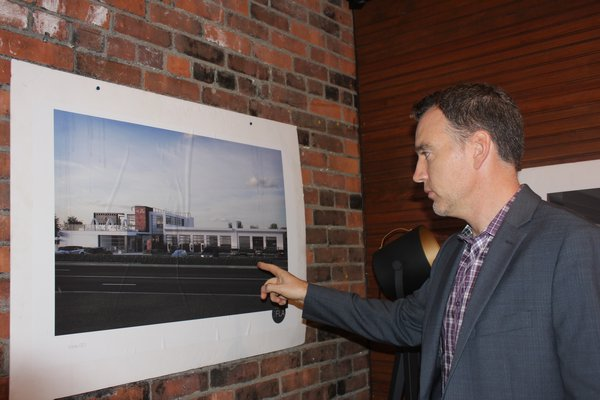 The Spur Founder Ashley John Heather points to a rendering of what the exterior of the building at 630 Hampton Road will look like once complete. PRESS FILE