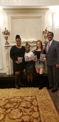 "Southampton girls basketball players Maddie Taylor, left, Allysha Thomas, Taylor Pike and theit head coach Richard ""Juni"" Wingfield with their postseason awards this past winter."