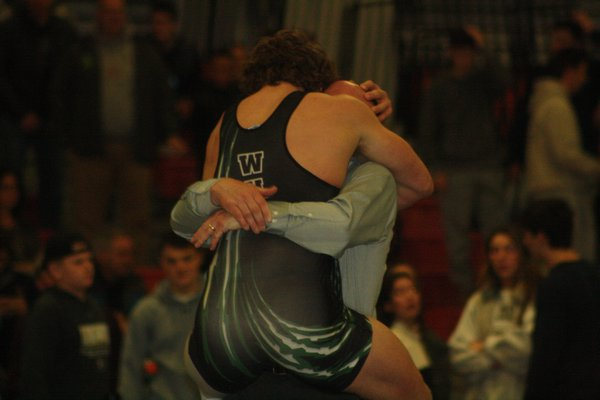 Westhampton Beach senior Liam McIntyre jumps into the arms of head coach Paul Bass after winning his second straight county title. CAILIN RILEY