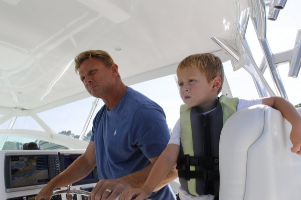 Gregg Desantis, Center Moriches boater and resident, takes his sons out for a ride on his 40-foot boat in Moriches Bay. KATE RIGA