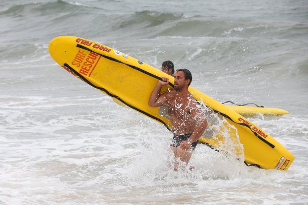 Ethan Mitchell comes out of the water with his board.