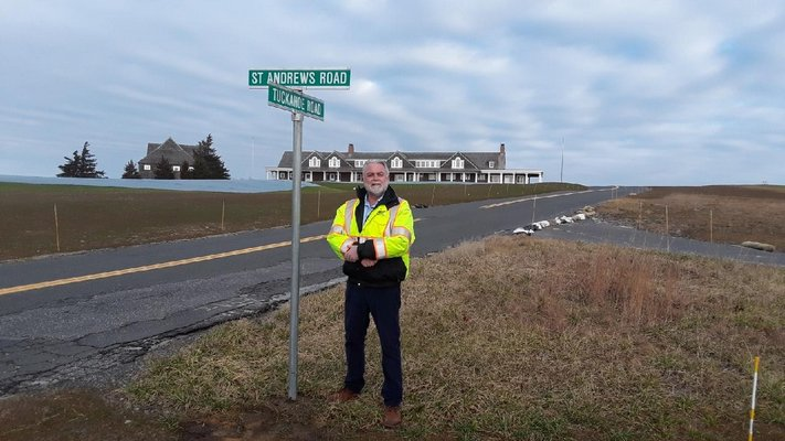 Southampton Town Highway Superintendent Alex Gregor next to a newly installed sign at the intersection of Tuckahoe Road and St. Andrews Road, on December 31, 2018. COURTESY ALEX GREGOR