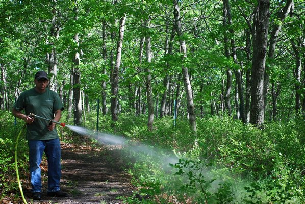 Brian Kelly of East End Tick & Mosquito Control sprays down one of his Southampton properties. By COURTESY WORDHAMPTON