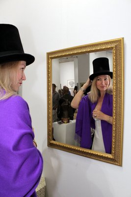 Elena Korneeva tries on one of Kevin Berlin's top hats. TOM KOCHIE