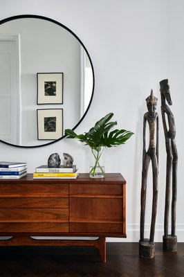 In a newly constructed home's foyer, a mid-century credenza is enjoyed while a set of African statutes is admired. CHRISTIAN HARDER