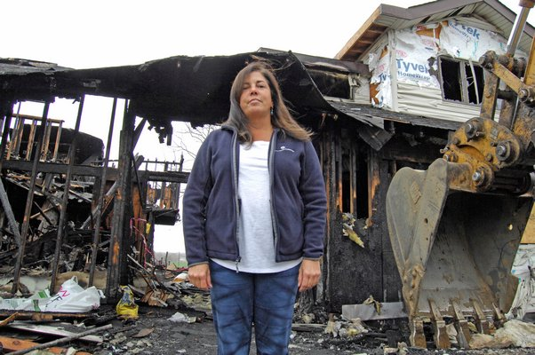 Theresa Kiernan stands before her home, which was destroyed by fire on March 3. The structure is set to be demolished on Monday.   DANA SHAW