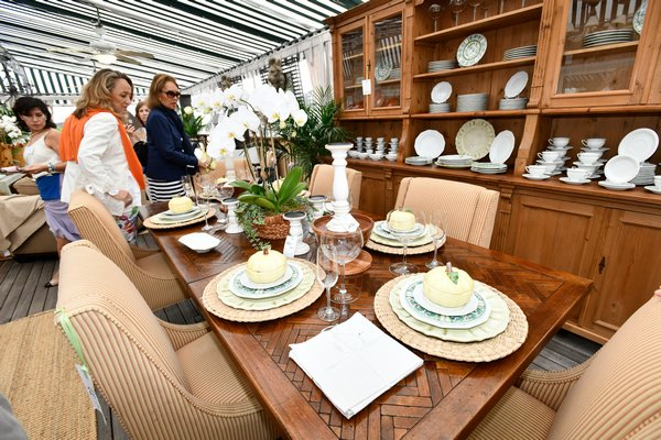 French country dining table in French cherry with parquetry top and coordinating breakfront being considered by several attendees early on in the sale. Everything sold in this beautiful vignette including the place settings and accessories. DANA SHAW