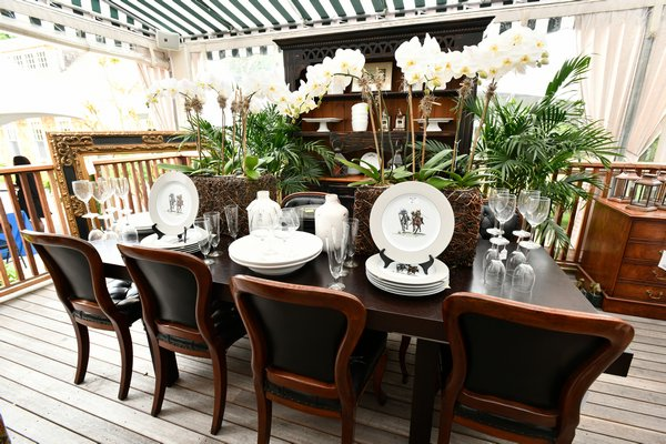 The setting including a French provencal walnut table with dark walnut hutch and French empire style chairs; accented with all white chargers, plates and white orchids. This setting, pulling together the dark woods with white accessories was classic country chic! DANA SHAW