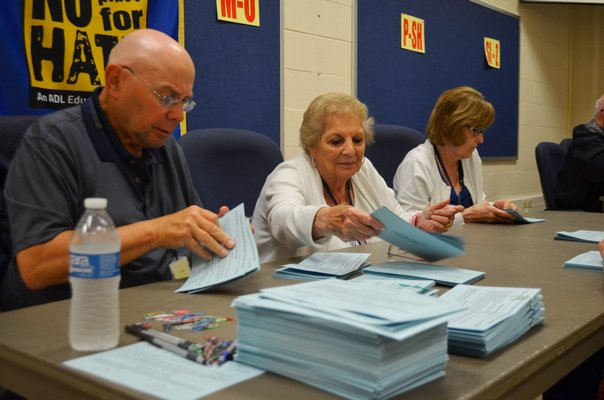 Paid election workers counted the nearly 1,700 votes by hand Tuesday night. ANISAH ABDULLAH