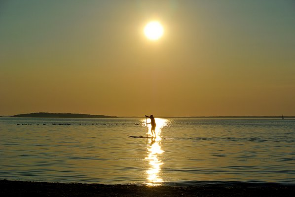 August 8: A paddleboarder heads in at sunset at Long Beach in Sag Harbor.