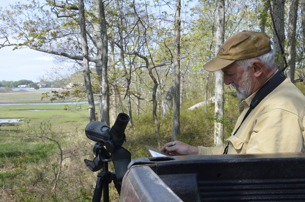 The Nature Conservancy's Preserve Manager Mike Scheibel makes a note that an osprey nest is active, after checking it out with his Swarovski scope. SHAYE WEAVER