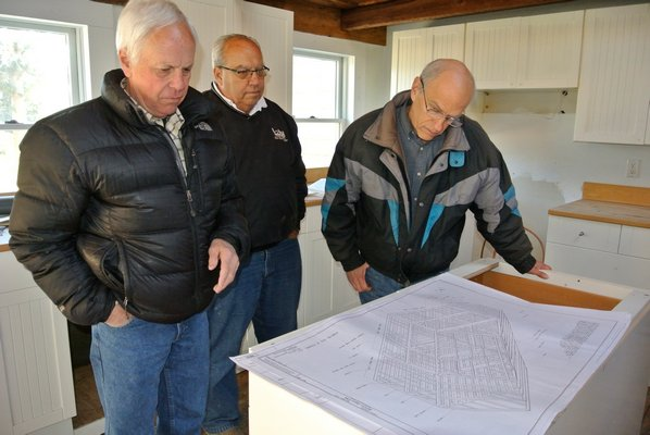 Larry Jones, builder Jim Zizzi and Bob Hirt look over the detailed plans for an East Hampton restoration project.