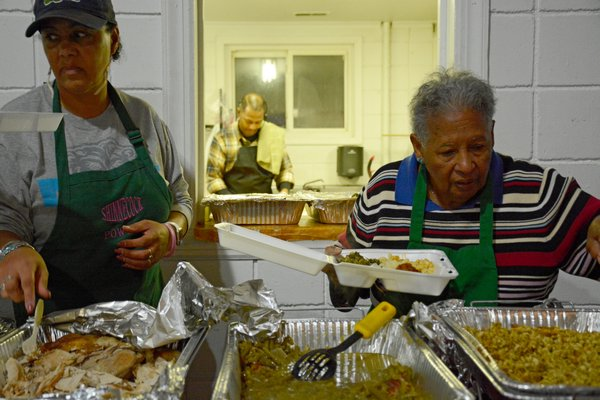 Lisa Goree and Loretta Reddick put together to-go containers for elders on the reservation who couldn't make the festivities. JD ALLEN