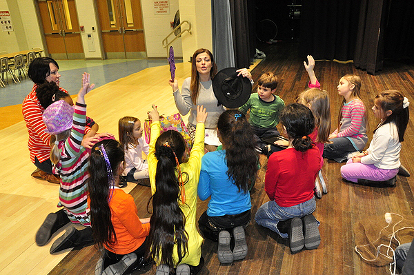 Kristen Poulakis, left, and Selina Pasca pass out props during Vaudeville Kids on the Hampton Bays Middle School stage. MICHELLE TRAURING