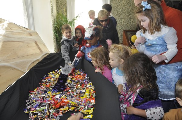 Trick-or-treaters grab a handful of candy at the Corwith House in Bridgehampton. MICHELLE TRAURING