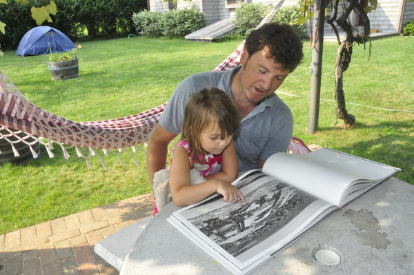"""Zak Powers flips through his photo book, """"Further Lane,"""" with his three-year-old daughter, Lyla, in Amagansett last week. MICHELLE TRAURING"""