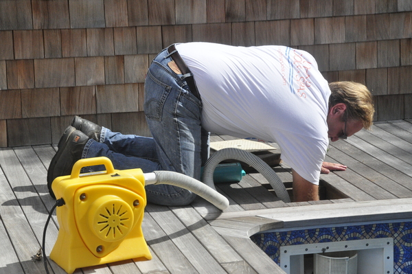 John's Pools & Spas executive manager Stanley Schorr blows out a skimmer in Quogue.
