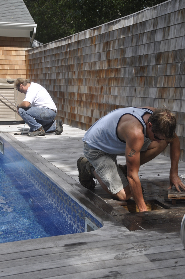 John's Pools & Spas pool technician Brad McNamara, front, and executive manager Stanley Schorr plug up skimmers in Quogue.